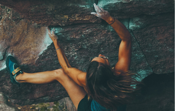 Toned woman climbing rocks with sunglasses on and chalked hands