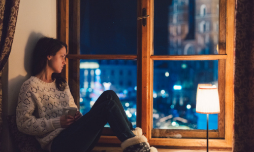 Girl sitting beside window at night looking sad
